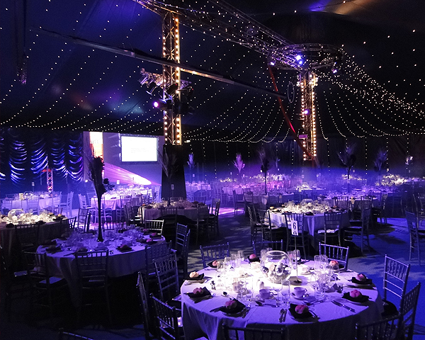 round tables set for dinner with lights and entertainment rigging from the marquee Bloomsbury Big Top Christmas Party WC1