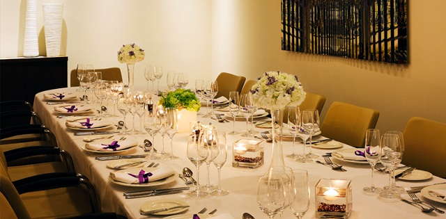 Marylebone Hotel Christmas Party London W1. Table set up for Christmas dining with candles on centre of table and flowers for decoration.