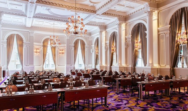 Ballroom set up in classroom style with large wooden desks for a conference Corinthia London Venue Hire SW1