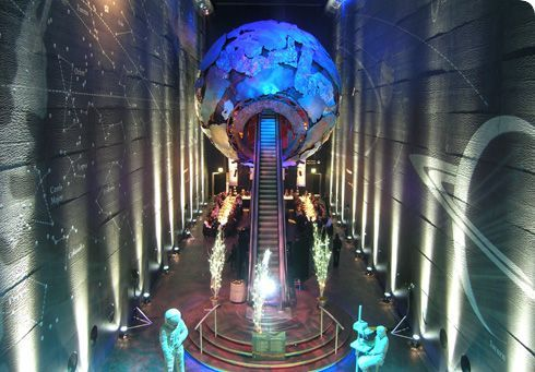 Earth Galleries with birds eye view of the escalator moving up into a globe and up lighters surrounding the room Natural History Museum Venue Hire SW7