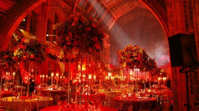 Hinzte Hall with red uplighters and round tables decorated with extravagant floral decor Natural History Museum Christmas Party SW7