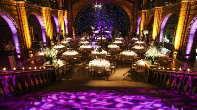 Hinzte Hall set for a large sit down dinner with purple uplighters and tables dressed in white linen with light patterns reflected onto the floor Natural History Museum Christmas party SW7