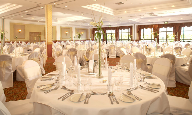 Lydiard Suite set for a Christmas party with round tables dressed in white linen with centre pieces and lots of natural daylight with place settings Hilton Swindon Christmas Party SN5