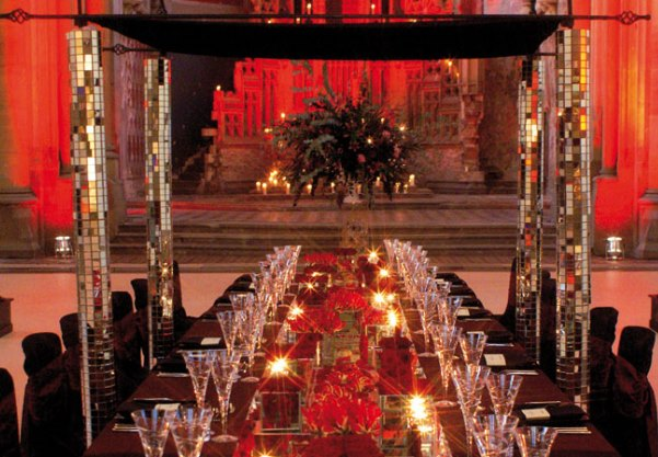 Monastery Manchester Venue Hire M12 table dressed in red linen with candles for a Banquet at the Monastery Venue Hire M12