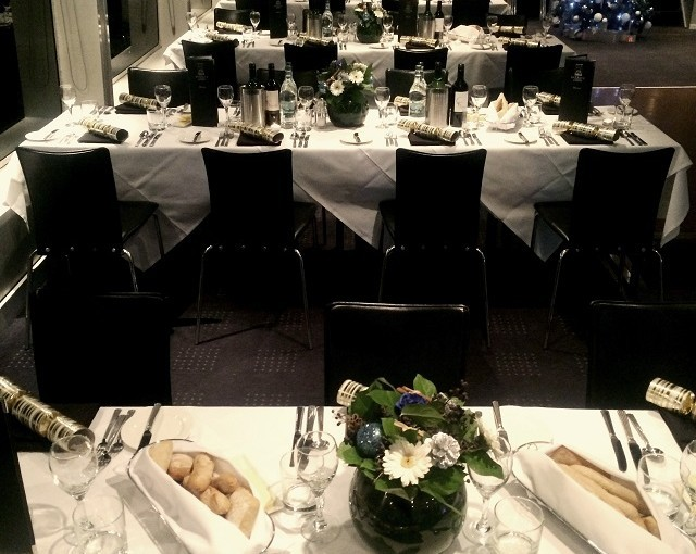 Banqueting tables set in rows laid for a Christmas party with crackers and centre pieces Bateaux London Christmas Party WC2