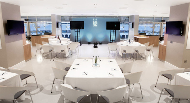 tables dressed in white linen in cabaret style of a presentation on a stage in the Mancunian Suite Manchester City Football Club Venue Hire M11