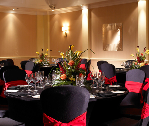Marriott Heathrow Windsor Hotel Christmas Party SL3. Dining area set up for christmas dinner. Round tables with decorated chairs with red ribbon around each chair.