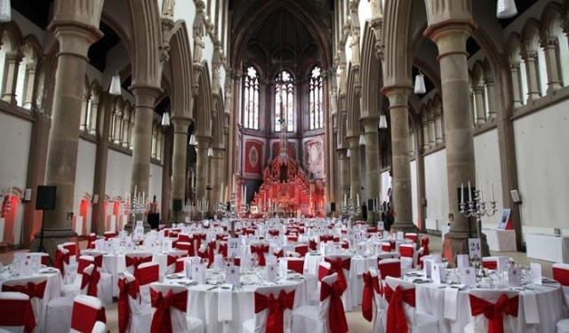 Monastery Manchester Venue Hire M12 Round tables dressed in white linen with red bow chair covers at the Monastery Christmas Party M12
