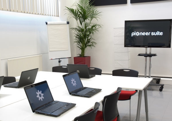 informal meeting set out with laptops and presentation screen in the Pioneer Suite Venue Hire M1