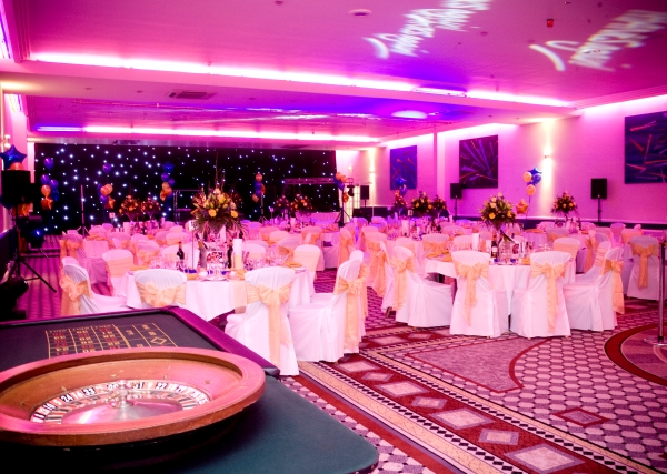 Function Room set for a large Christmas party with bright pink uplighters with casino tables set up as entertainment in the corner of the room Jurys Inn Hinckley Island Hotel Christmas Party LE10