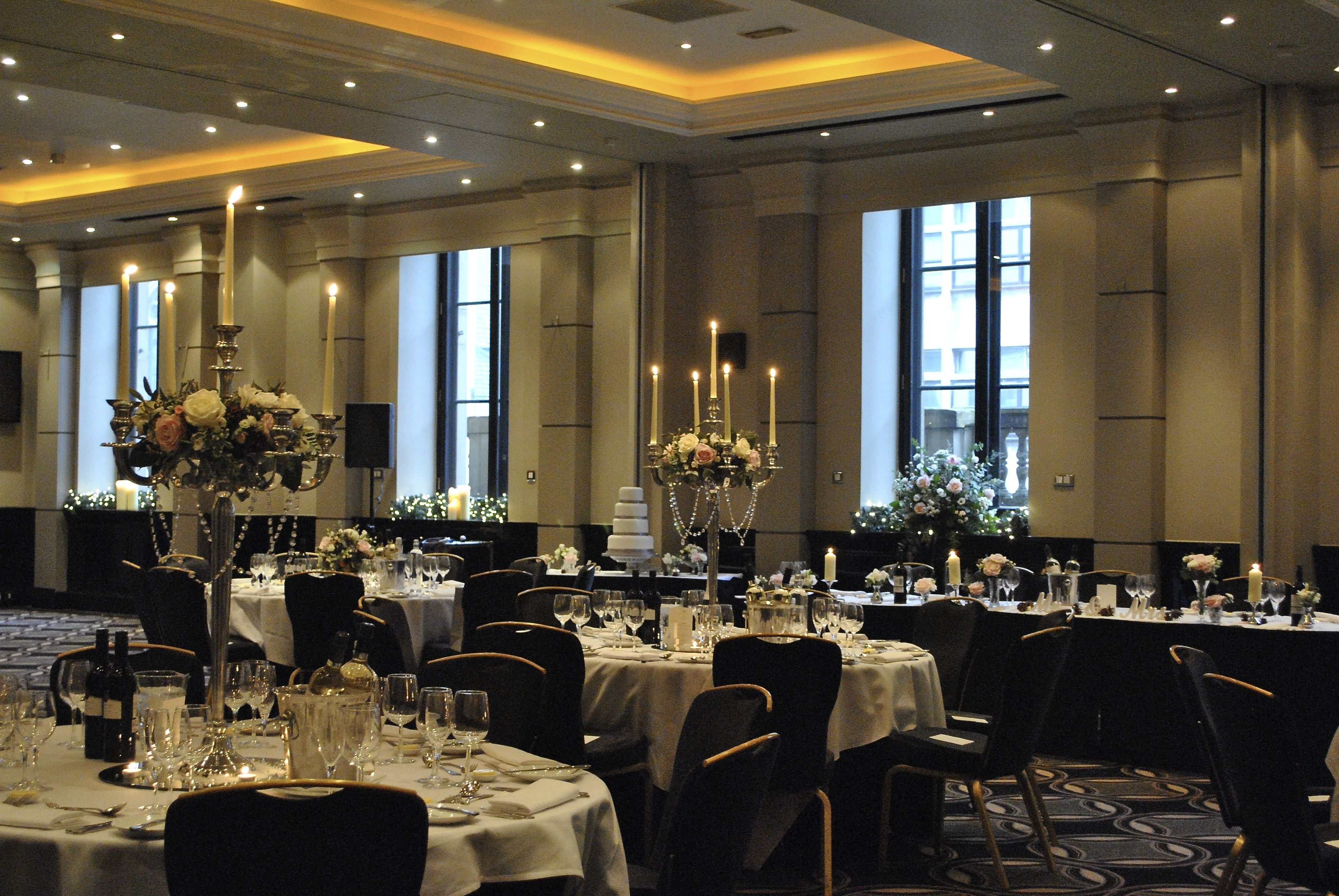 Round tables dressed in white linen and set for a dinner party in the Halle Suite Radisson Blu Edwardian Manchester Christmas Party, M2