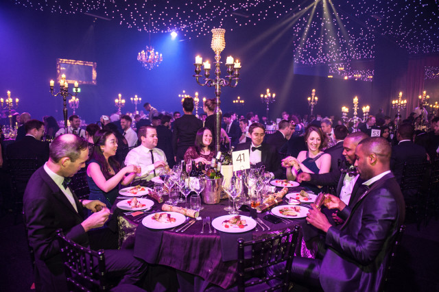 Guests enjoying a 3 coure meal with round table decorated with candelabra EventCity Christmas Party M41