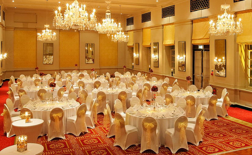 Dinner layout with white table linen and chair covers with bows in the George V Bloomsbury. Bloomsbury Street Hotel Christmas Party WC1