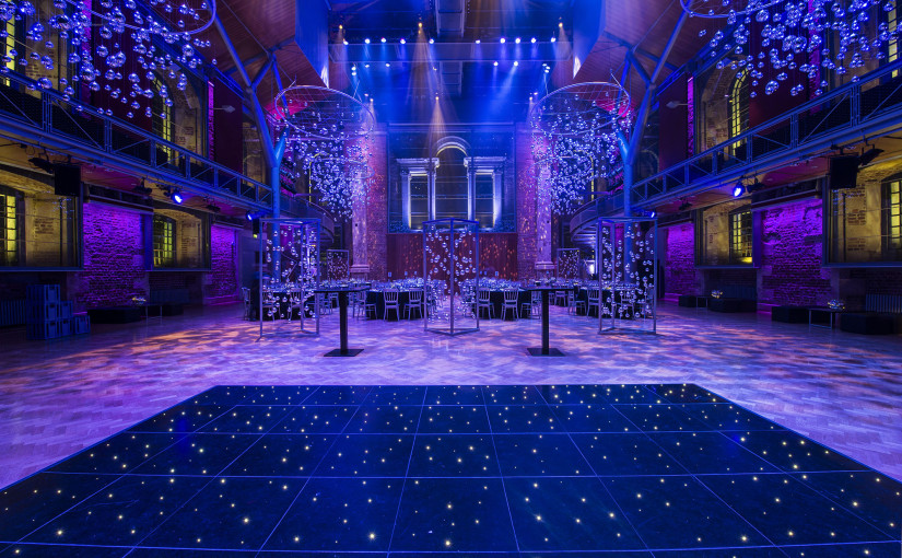 set up for a diner dance with round tables purple mood lighting and a stat lit dance floor at LSO St Luke's Christmas Party EC1