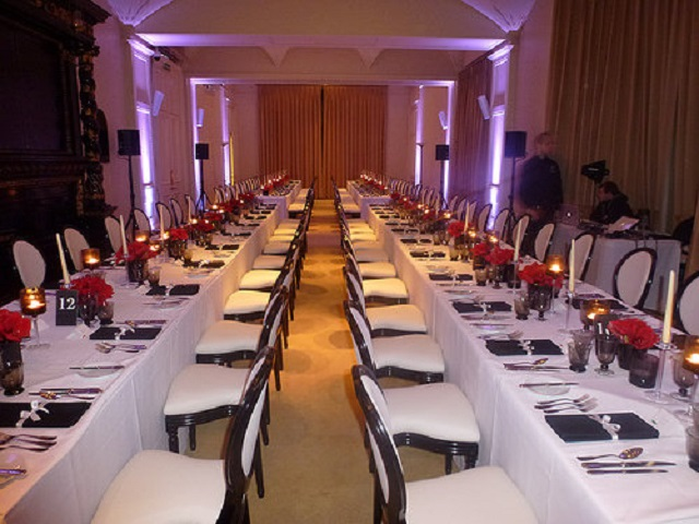 Kent House Knightsbridge Christmas Party SW7. long tables set out for christmas dining. with white table cloth and red roses and candles lit.