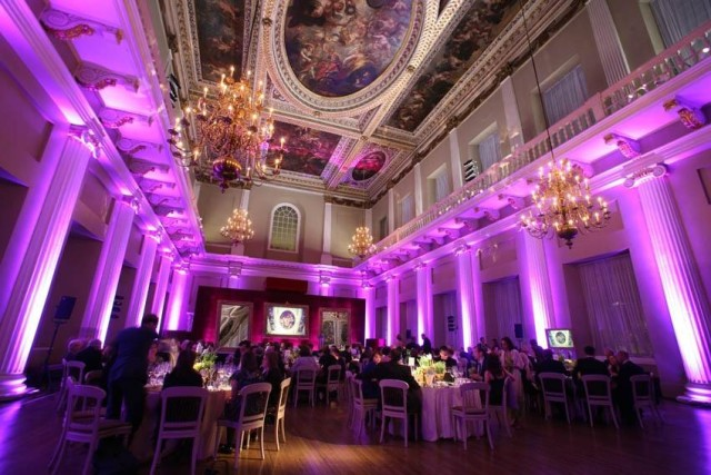 Main Hall set for a grand Christmas dinner with purple uplighers around the room with views of the grand portrait ceiling Banqueting House Christmas Party SW1