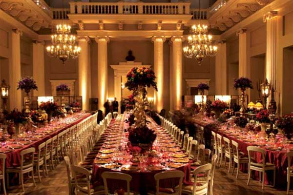 Main Hall set for a large banquet Christmas dinner with long tables dressed with large floral centre pieces Banqueting House Christmas Party SW1