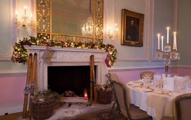 Chandos House Christmas Party W1. Seating area with armchairs in front of fireplace decorated with Christmas decorations.