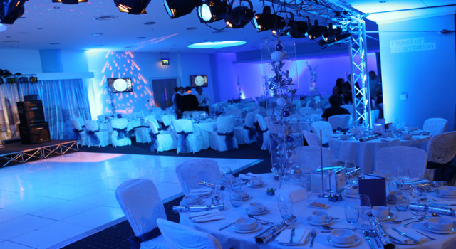 Blue mood lighting with round tables dressed for Christmas party surrounding a dance floor in the commonwealth suite at = Manchester City Football Club Christmas Party M11