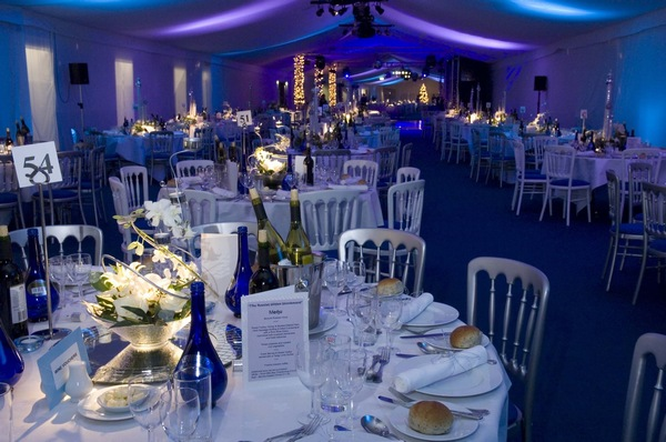 Round tables dressed in white linen for a dinner in the commonwealth suite at Manchester City Football Club Shared Christmas Party M11