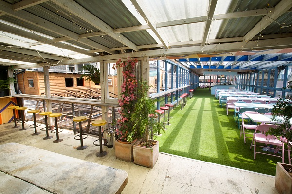 Dinerama Summer Party EC2. Pavillion of venue with tables and chairs bar and skyline with fake grass adding to the feel of being outside.