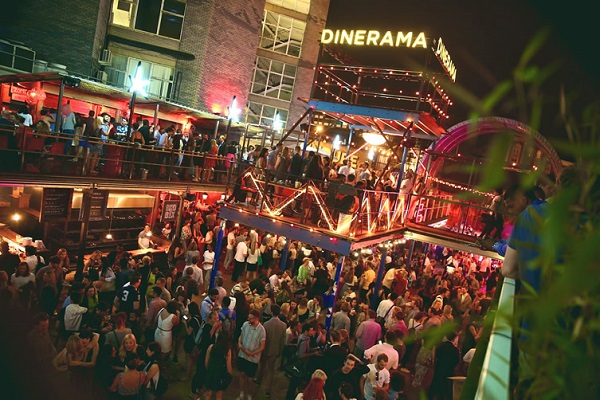 Dinerama Summer Party EC2. Birds eye view of Dinerama of guests enjoying their evening. With roof detached and lights on as