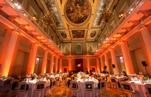 Main Hall set for a grand christmas dinner with orange uplighers around the room with views of the grand portrait ceiling Banqueting House Christmas Party SW1