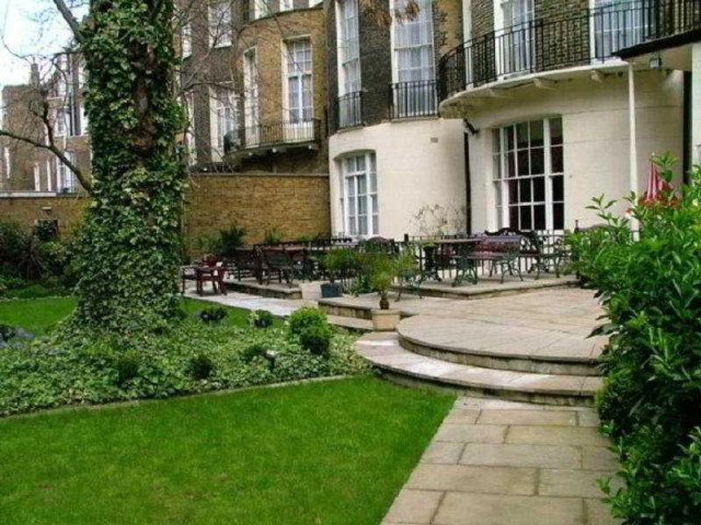 View of the garden with patio leading to conservatory at the Grange White Hall Venue Hire WC1