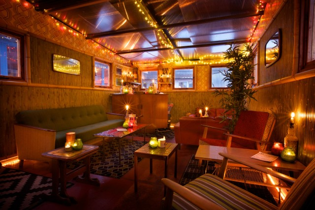 House Of Bamboo all lit with cosy candles and retro furniture with small high windows for natural light Dinerama Christmas Party EC2
