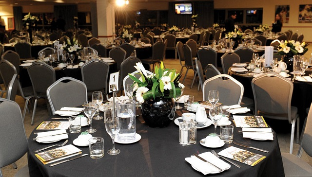 Set up for christmas dinner wth round tables and boutique grey chairs with white tulips on tables as centre pieces. Kia Oval Shared Christmas Party SE11