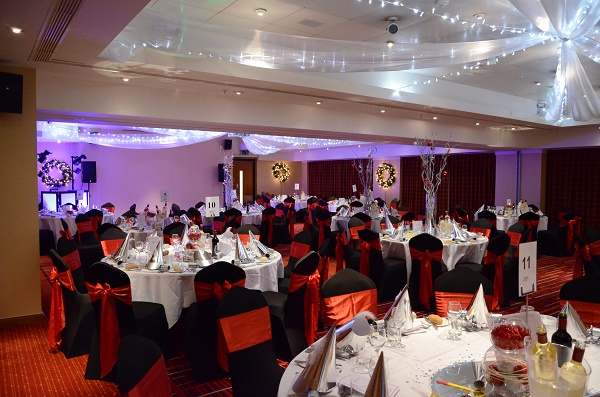 Cheshire Suite with round tables dressed for a Christmas dinner Manchester Airport Marriott Hotel Christmas Party WA15