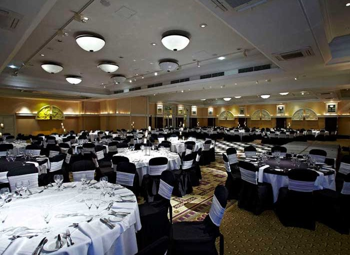 Alexandra Suite set up for a dinner with round tables dressed in black linen with white chair covers at the Midland Hotel Venue Hire M60