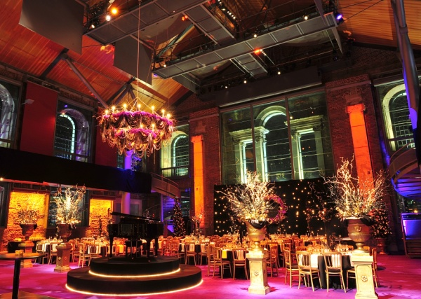 view of the main space with round tables dressed for dinner with chandelier LSO St Luke's Christmas Party EC1