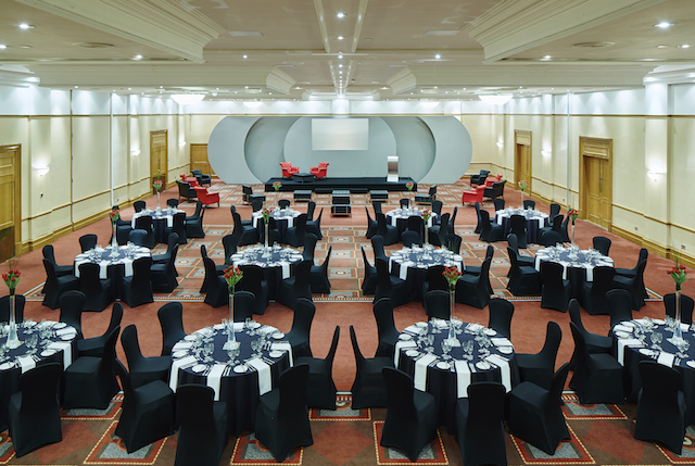 Bristol Marriott Hotel City Centre Christmas Party BS1. Large room with round tabes and chairs set up banqueting style for a christmas event.