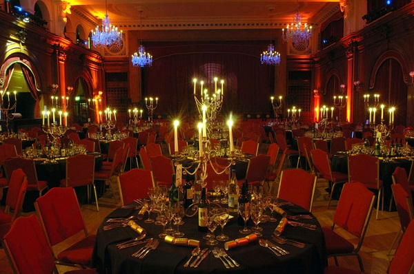 Speakeasy Ball Christmas Party W2. Showing tables and chairs set up banqueting style. With red chairs and round tables with centre pieces as candles