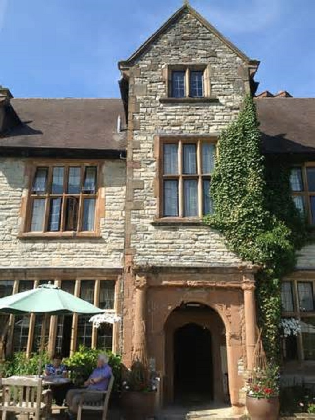 Billesley Manor Hotel Venue Hire B49. Photo of the outside of historic building. with outside seating. tables and umbrellas.