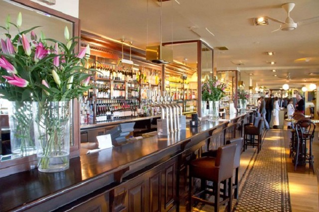 Browns Butlers Wharf Venue Hire SE1. Photo of long bar with flower to add colour to the contempary feel of venue.