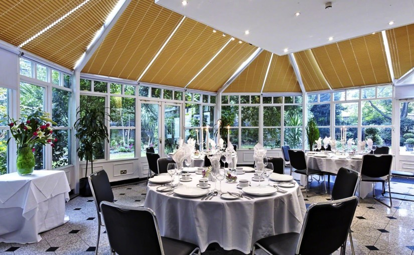 Conservatory with round tables set up for summer lunch with natural daylight Grange White Hall Venue Hire WC1