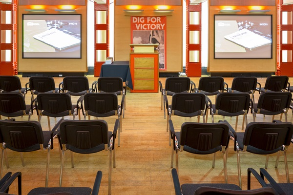 Churchill War Rooms Venue Hire SW1. Inside of CWR of a conference set up with screen at front of chairs set up theatre style.