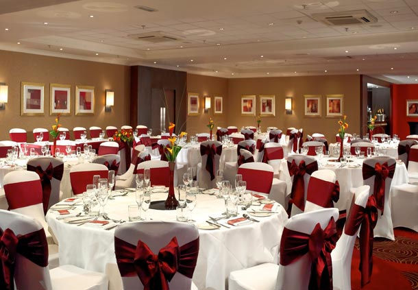 Marriott Hotel Edinburgh Christmas Party EH12. Tables set out for a events dinner. round tables with chairs decorated with red bows.