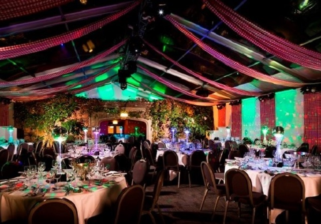 Kensington Roof Gardens Christmas Party W8, colourful tent style roof large round tables laid for dinner