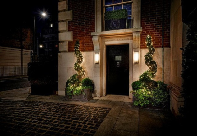 London Marriott Hotel Grosvenor Square Christmas Party W1. Outside of London Marriott. With festive plants next to entrance, either side.