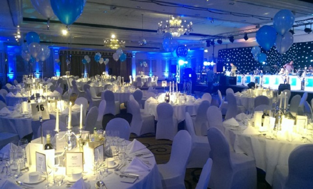 London Marriott Hotel Grosvenor Square Christmas Party W1. Dining area set up for chrostmas dinner. All white furnishings with festive coloured lights.