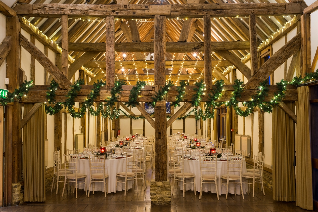 Loseley Park Christmas Party GU3, tinsel on beams in the barn
