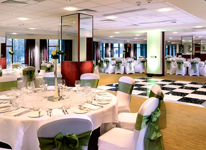 Piccadilly Suite with dance floor and round tables dressed for a Christmas dinner dance Macdonald Manchester Hotel Christmas Party M1