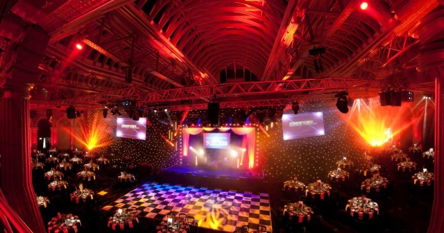 Old Billingsgate Venue Hire EC3, large seated dinner set up, company theming, large screens, high ceilings
