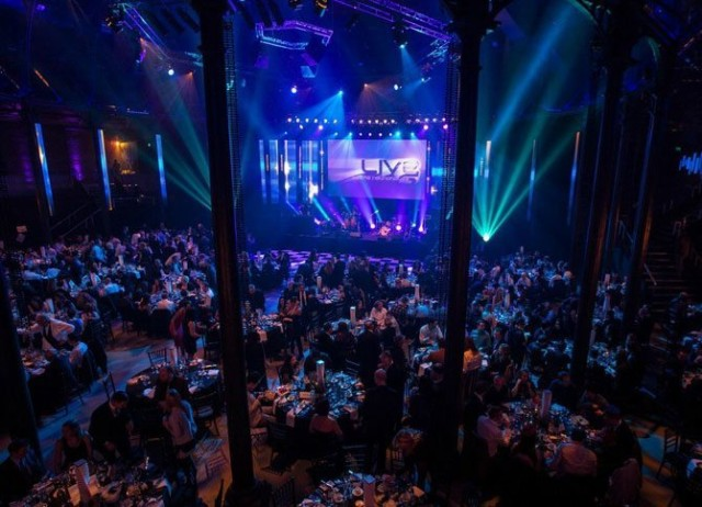 Roundhouse Christmas Party NW1, birds eye view of the seated dinner set up, large screen at the front of the room, mood lighting, stunning Christmas theming