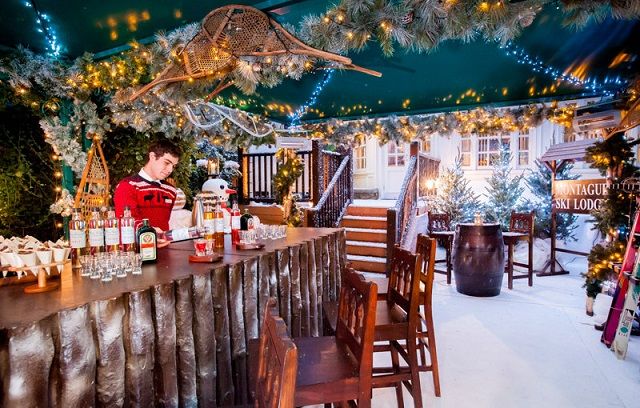 Snow decorated with wooden bar and festive lights inside the Montague's Ultimate Ski Lodge Christmas Party WC1