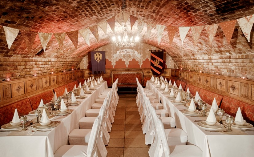 Banqueting Tables set out for a Christmas party with exposed brick work and table settings Ivory Vaults Christmas Party E1