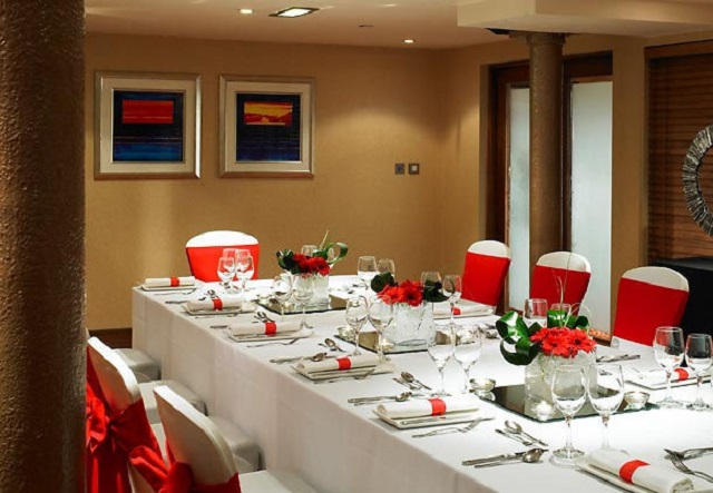 Manchester Marriott Victoria Albert Hotel Christmas Party M34 . Dining room table set up woth chairs. Decorated with red chair covers and red flowers on table
